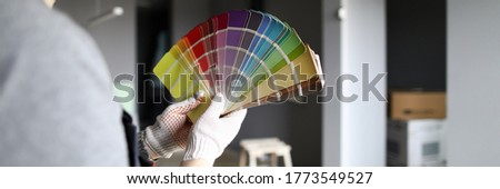 Close-up of palettes samples in hands of handyman. Decorating and designing interior, repainting walls with bright colors. Choice of material, selection of tints