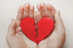 Close up of paper broken heart on white wooden background