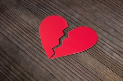 Close up of paper broken heart on wooden background