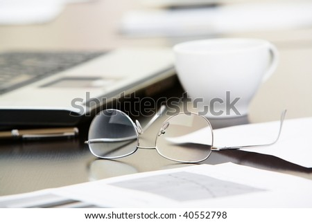 Close-up of papers, glasses and cup on workplace