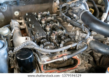 Close up of parts in a car engine twins camshaft system with Roller timing chain. - Overhaul servicing of vehicle #1379596529
