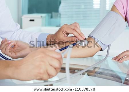 Close-up of patient�¢??s arm during blood pressure measuring at medical consultation