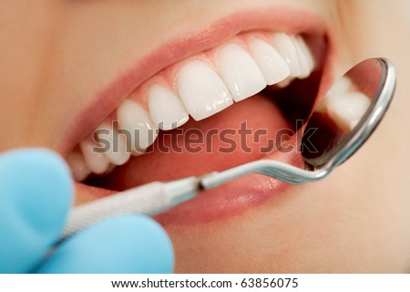 Close-up of patient s open mouth during oral checkup with mirror near by