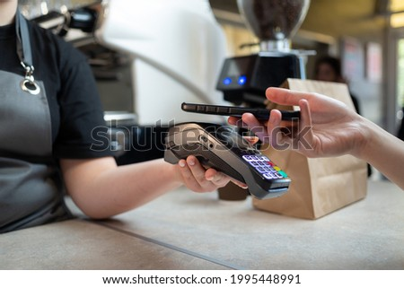 Close-up of payment by phone with N FS technology on the phone with a contactless terminal in a cafe shop or cafeteria. Mobile phone or smartphone for order payment with n fs technology. Foto stock ©