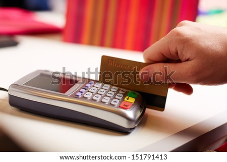 Close-up of payment through machine by plastic card