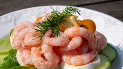 Close up of peeled fresh shrimps on white bread, making a delicious Swedish shrimp sandwich (räkmacka). Seafood and food preparation concept.