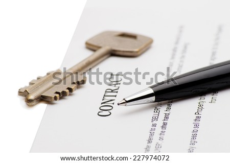 Close-up of pen on contract and key