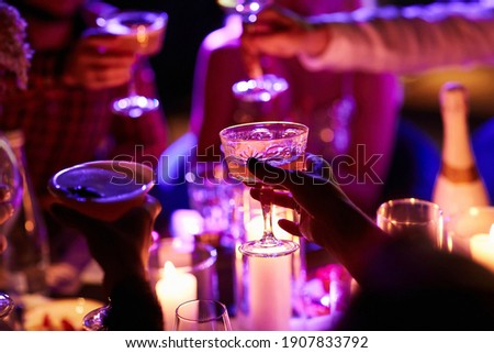 Close up of people drinking cocktails in restaurant. People having good time, cheering and drinking cold cocktails, enjoying friendship together in restaurant, close up view on hands.