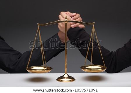 Close up of people fighting together in front of scale balance. Arm wrestling. Conflict of interest. Concepts of law and justice.