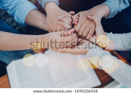 Close up of  people group holding hand and pray together over a blurred holy bible on wooden table, christian fellowship  or praying meeting in home concept with copy space
