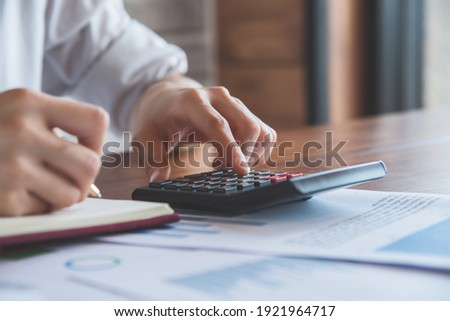 Close up of people hand work with calculator for business and finance.