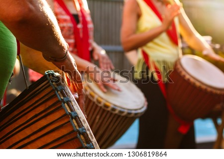 Close-up of people's hands playing on African djembe drums on a sunny summer evening.