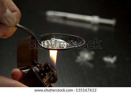 Close up of person cooking heroin using lighter