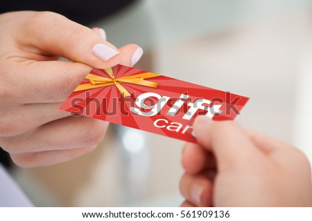 Close-up Of Person Hand Giving Gift Card To Another Person #561909136