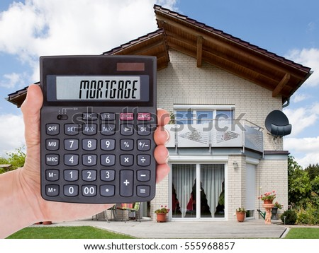 Close-up Of Person Hand Holding Calculator Calculating Mortgage Outside The House