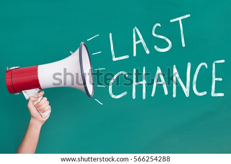 Close-Up Of Person Hand Holding Megaphone with Last Chance Announcement On Blackboard
