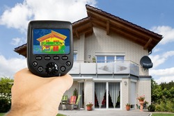 Close-up Of Person Hand Recording Heat Loss With Infrared Thermal Camera Outside The House