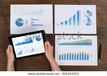 Close-up Of Person Hands Analyzing Financial Charts At Desk