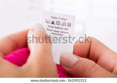 Close-up Of Person Reading The Clothing Label Showing Washing Instructions #561901312