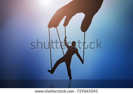 Close-up Of Person's Hand Controlling Puppet Man Against Blue Background #729665041