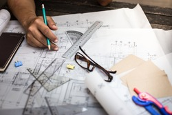 Close-up Of Person's Hand Drawing Plan On Blue Print with architect equipment.