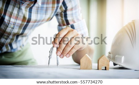 Close-up Of Person's Hand Drawing Plan On Blue Print with architect equipment #557734270