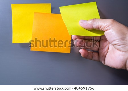 Close-up Of Person's Hand Holding Blank Yellow Note Sticked On Fridge Door #404591956
