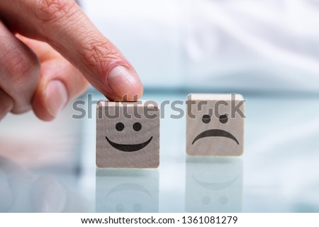 Close-up Of Person's Hand Holding Wooden Block With Happy And Unhappy Face On Reflective Desk #1361081279