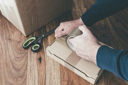 close-up of person sealing up shipping box with parcel tape, pruchase return and return of goods concept