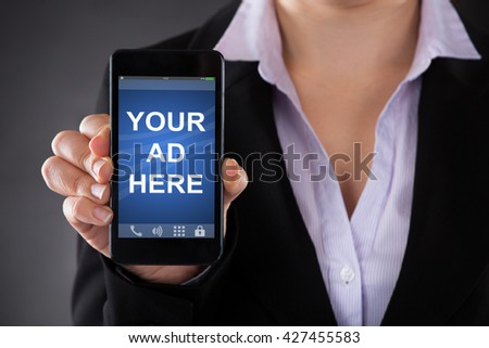Close-up Of Person Showing Your Ad Here Text On Mobile Phone Against Grey Background #427455583