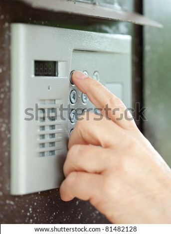 Close-up of person using building intercom