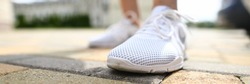 Close-up of person wearing shiny white sneakers. Macro shot of adult feet in shoe for running. Casual style for city life. Comfortable footwear and sport concept