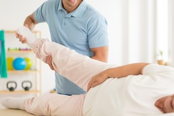 Close-up of personal physiotherapist rehabilitating senior woman's joints after hip reconstruction