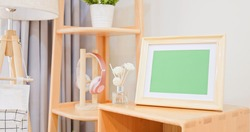 close up of photo frame with green copy space on cabinet in living room at home