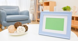 close up of photo frame with green copy space on desk in living room at home