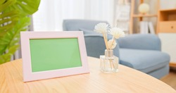 close up of photo frame with green copy space on table in living room at home