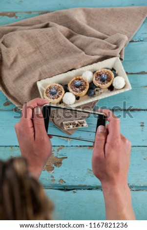 Close-up of photographer clicking a picture of dessert using smartphone