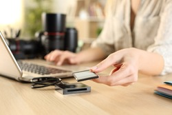 Close up of photographer woman hands plugging memory card to laptop on a desk at home