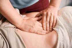 Close up of physician hands massaging woman abdomen during medical examination. Doctor examining patient stomach in clinic. Concept of healthcare, therapeutic massage and medical examination.