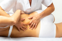 Close up of physiotherapist manipulating female lower spine. Rear view of girl laying on spa bed on her side.