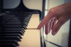 Close up of pianist forefinger touching piano key.