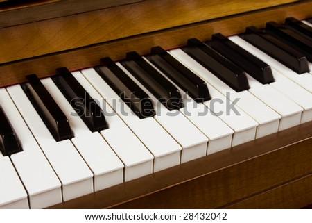 Close up of piano keys from a walnut piano.