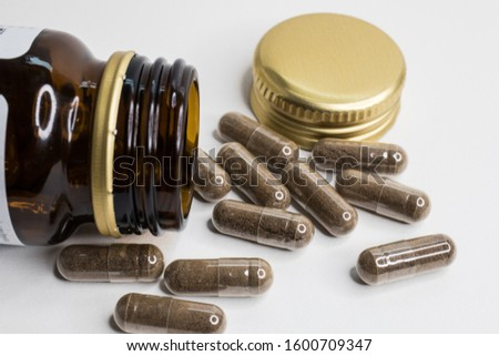 Close-up of pictures of vials and capsules of many capsules on a white background.