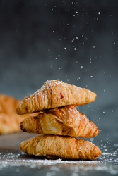 Close up of pile of delicious croissants on a dark background. Homemade croissants. Sugar glass falling. Vertical.