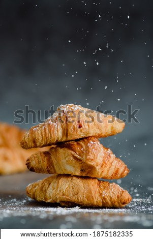 Close up of pile of delicious croissants on a dark background. Homemade croissants. Sugar glass falling. Vertical.  Сток-фото ©