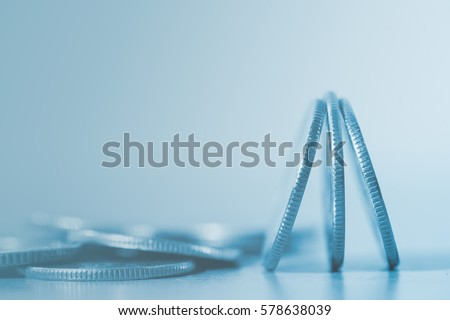 Close up of pile of silver  coins over soft background in blue tone with copy space for finance business and banking concept