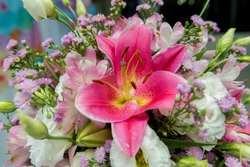 Close up of pink lily flowers around by roses, carnation flowers and green leaves. Close up of beautiful colorful bouquet of flowers with lily and roses. Different kind of flowers. Selective focus.