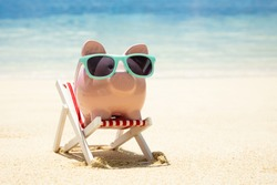 Close-up Of Pink Piggybank With Turquoise Sunglasses On Miniature Deck Chair On Sand At Beach