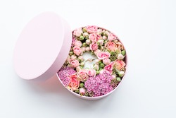 Close up of pink round box with golden ring inside decorated with purple,green,beige flowers roses on white background.Floral romantic composition with jewelry for engagement present for bride.Wedding
