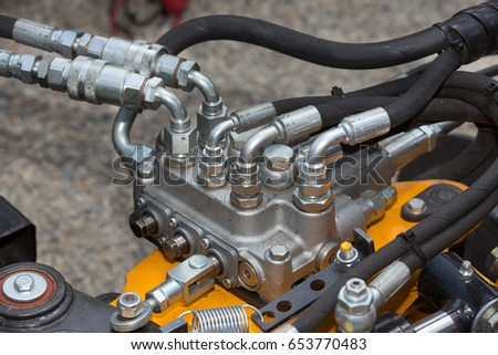 Close up of pipe system of hydraulic valves in agricultural machinery #653770483